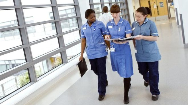 _95784478_c0151526-nurses_walking_along_hospital_corridor-spl